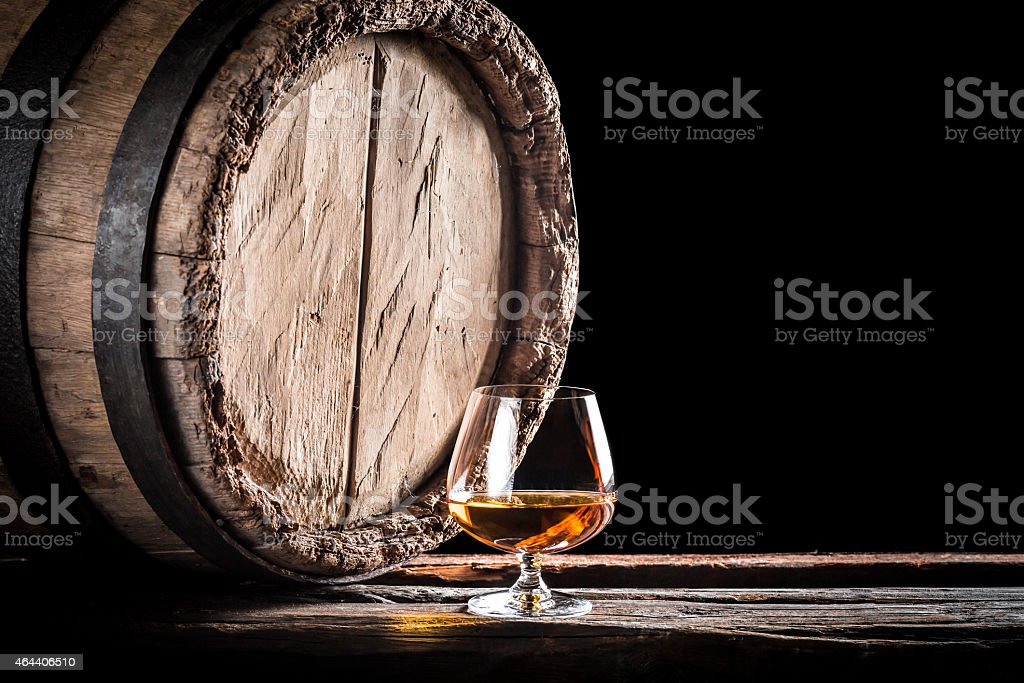 Old barrel and a glass of cognac stock photo