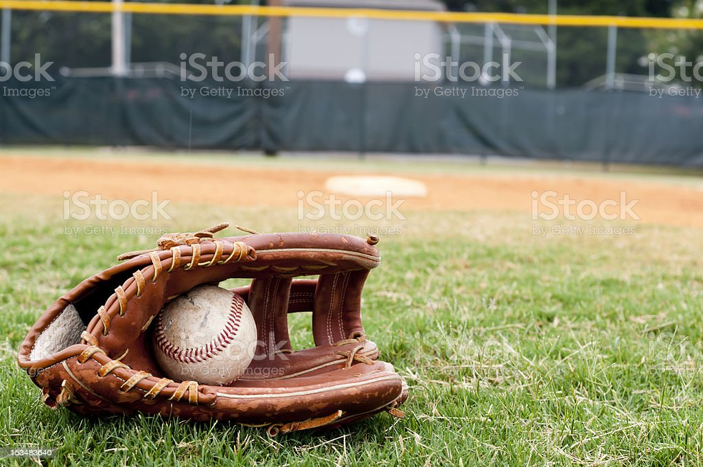 Old Baseball and Glove on Field stock photo