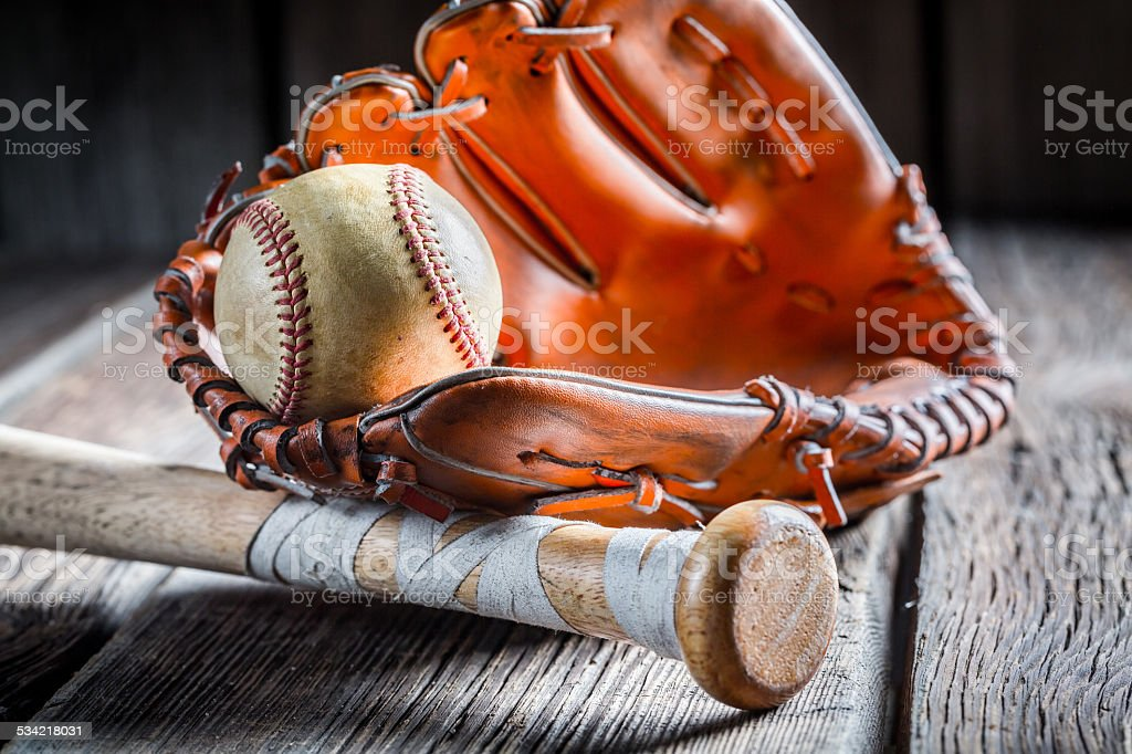 Old baseball ball and golden glove stock photo