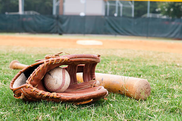 old baseball, glove, and bat on field - sports glove stock photos and pictures