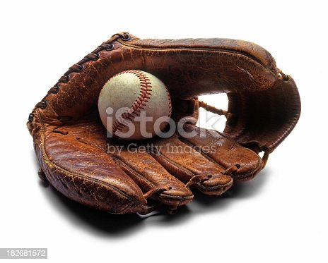 Old baseball sitting in an old glove