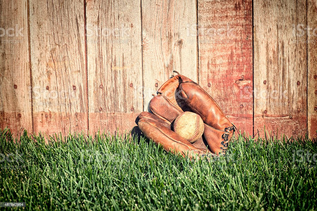 Old baseball mitt and ball on grass against wooden fence stock photo