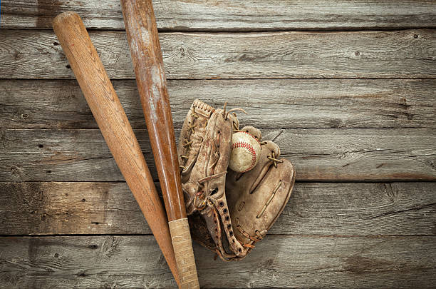 old baseball with mitt and bats on rough wood - baseball bat stock photos and pictures