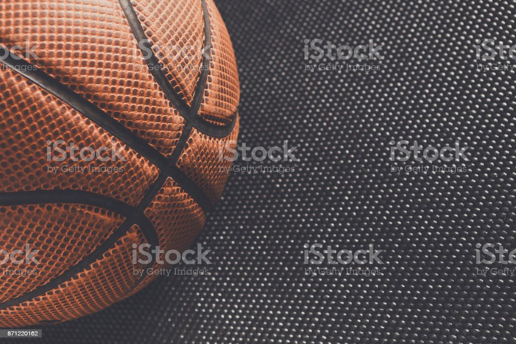 Old basketball ball on black background copy space stock photo