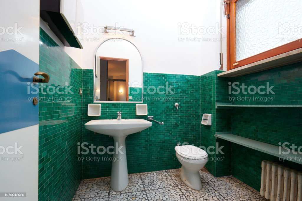 Old bathroom in normal apartment interior with green tiles in Italy
