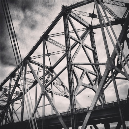 A moody black & white shot of the old Bay Bridge, with the cables of the new Bay Bridge in the foreground.  Taken with an iPhone and processed in Instagram.
