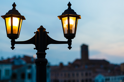 Old beautiful street lamp shines at evening