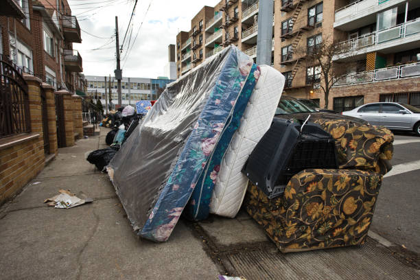 Old bed and mattress dumped along the street stock photo