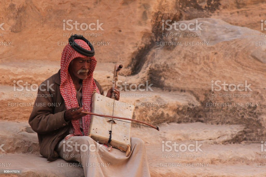 Old bedouin man with his self made oud performing in little Petra, Jordan stock photo