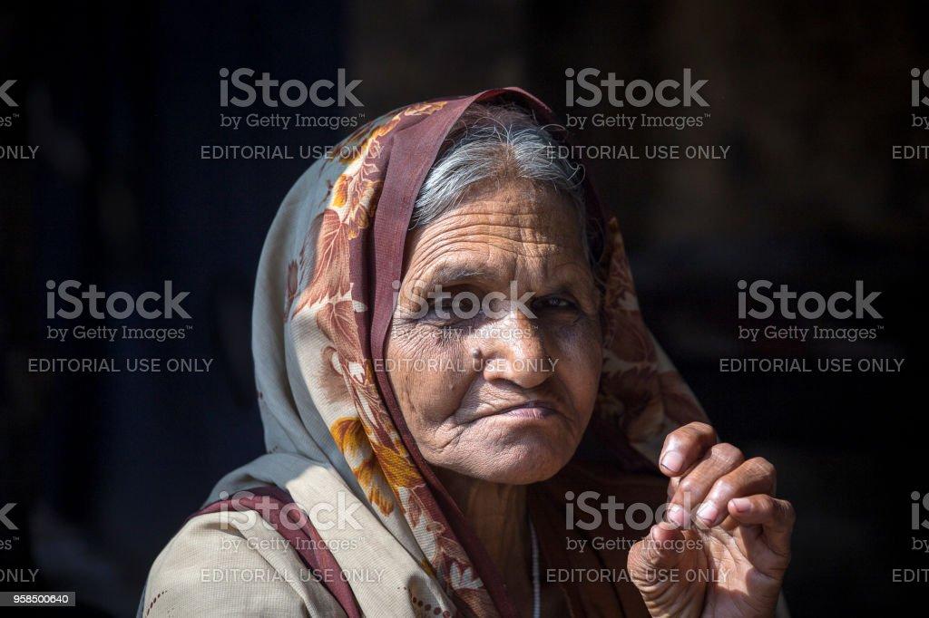 Old beggar woman on street at Dashashwamedh Ghat in Varanasi, Uttar Pradesh, India stock photo