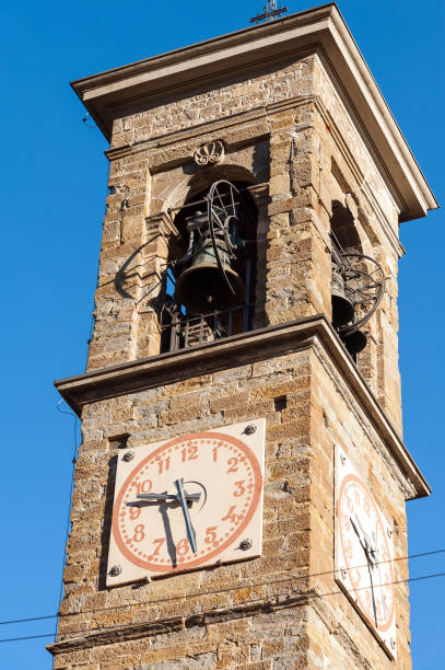 old bell tower with watches in bergamo town, italy - klokkentoren met luidende klokken stockfoto's en -beelden