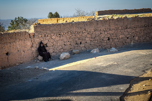 Aguegour, Morocco - January 20, 2018: Old berber man seated in a rock in Aguegour village, Al Haouz province, Morocco