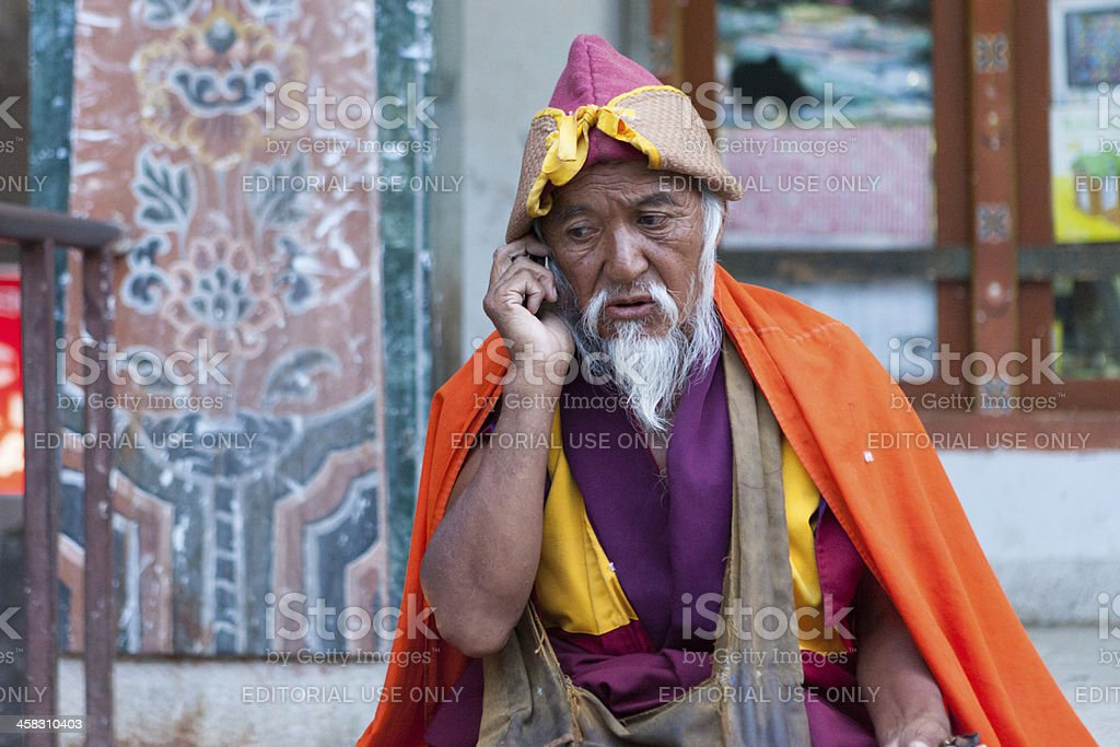 Old bhutanese monk making phone call in streets of Thimpu foto
