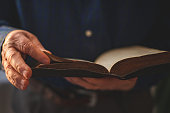 istock Old Bible in hands of an old man 1309802467
