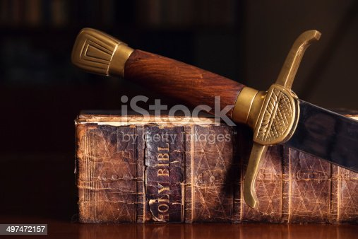 istock Old Bible With Sword 497472157