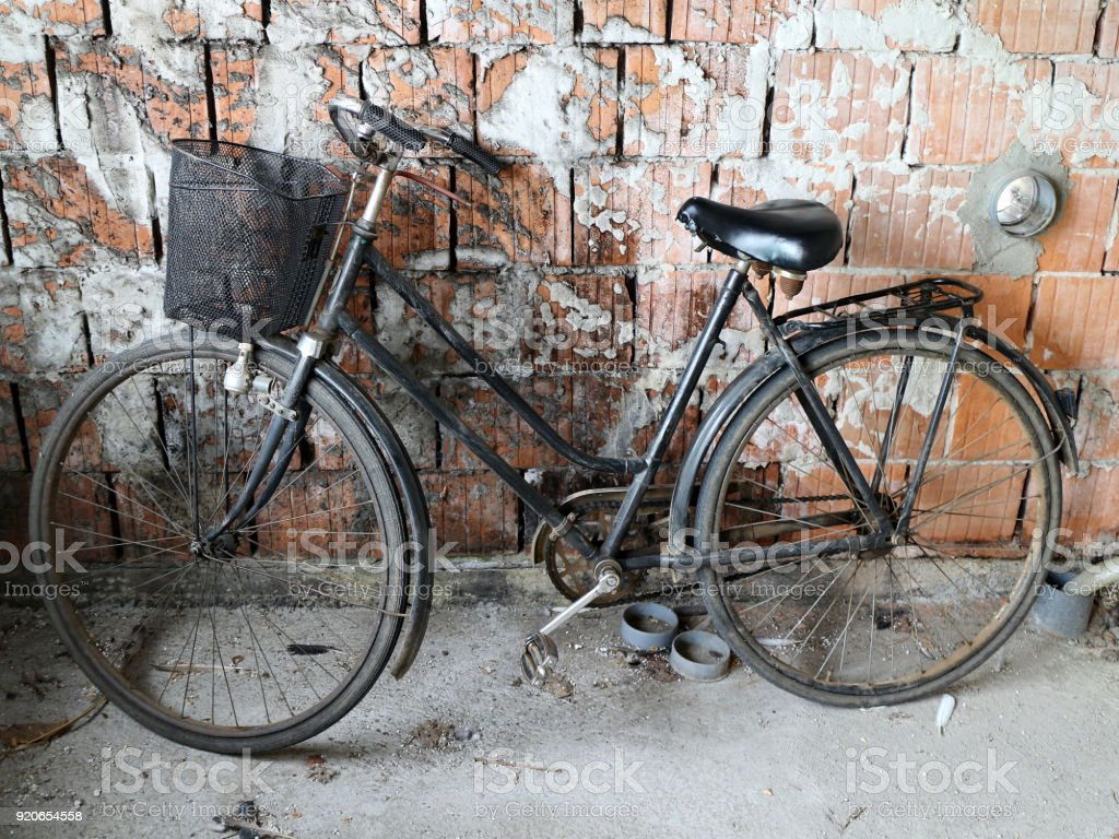 Old bicycle against a rustic wall stock photo