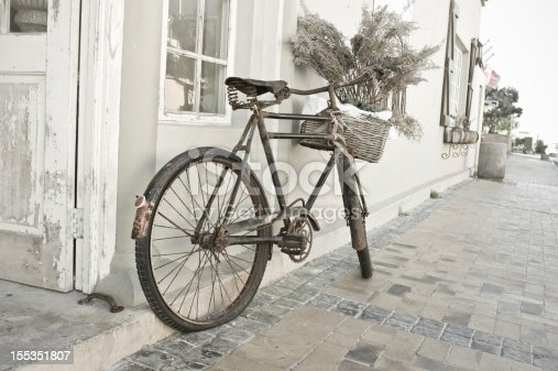 An old bicycle in Cape Town South Africa rests against a wall on a quiet street.  Street is brick and it is leaning against a white and grey wall.  Subdued colours.  Leica Camera Image.