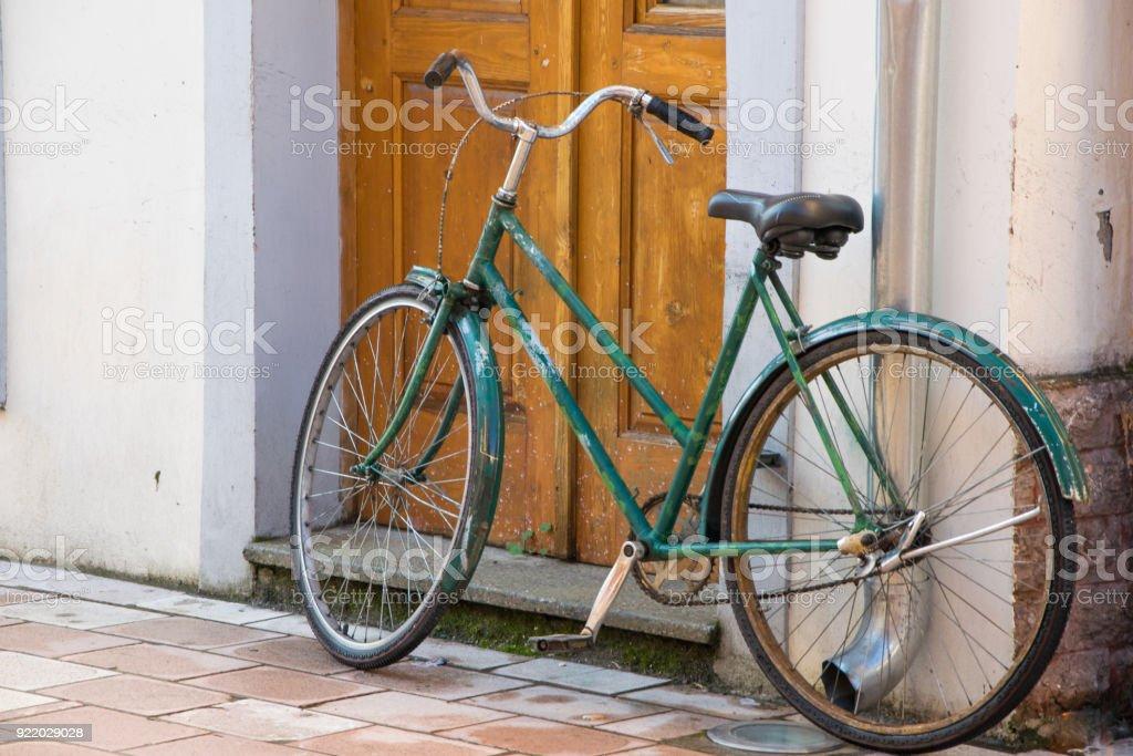 Antigua bicicleta delante de la puerta de la casa, tradicional medio de transporte para una vida sana - foto de stock
