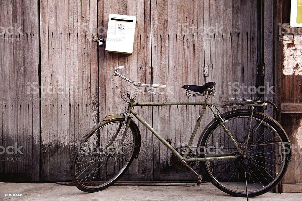 Old bicycle leaning up against a locked wooden door royalty-free stock photo