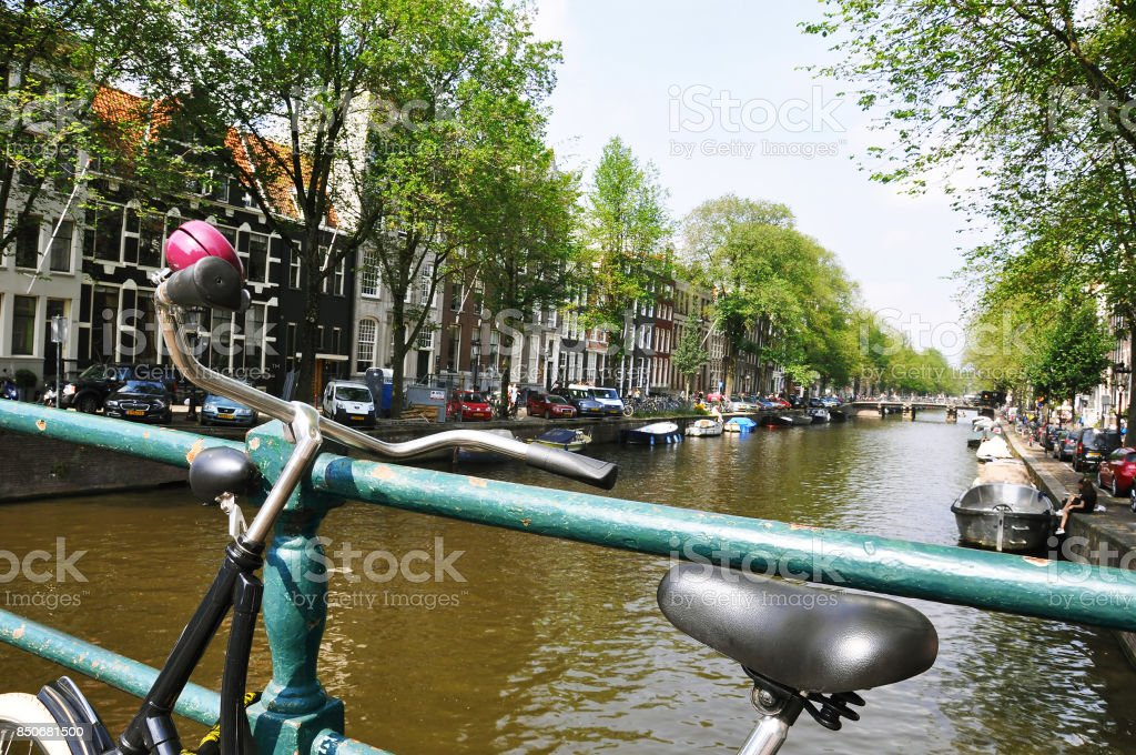 Old bicycle standing next to canal. Amsterdam cityscape stock photo