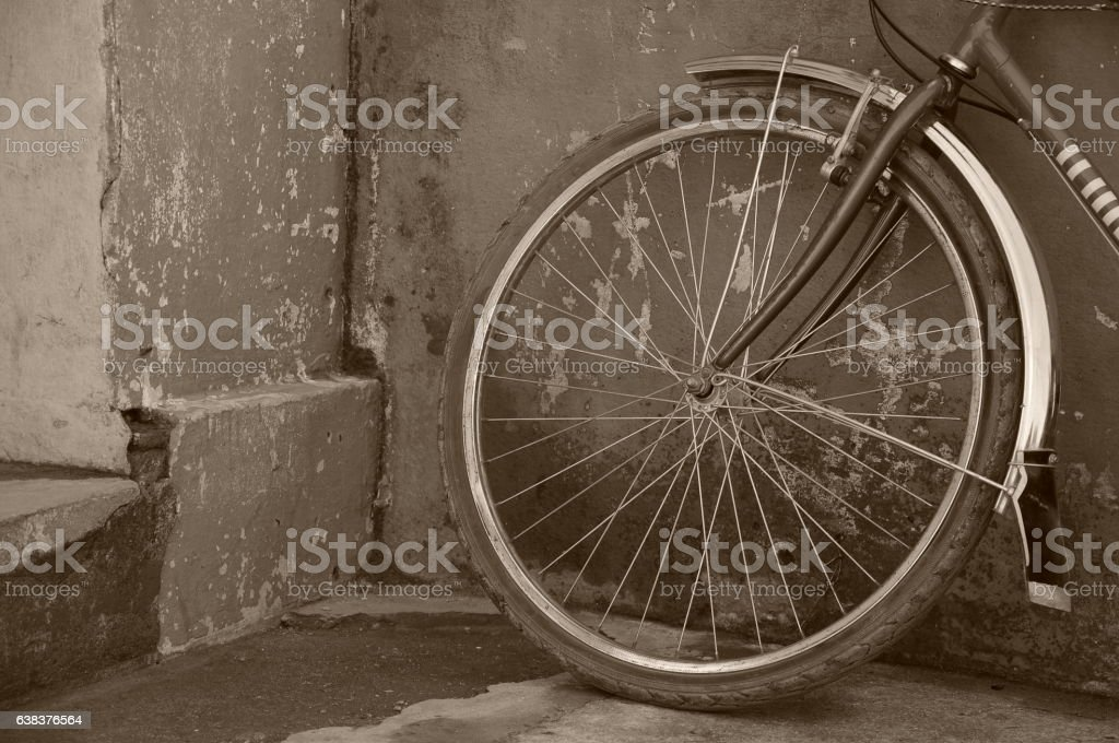 old bicycle tire leaning on old rusted wall stock photo