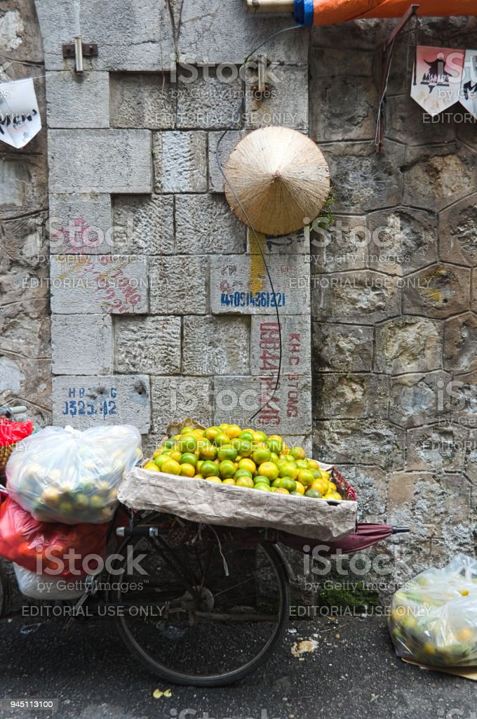 Old bicycle with oranges fruits on street market in Hanoi stock photo