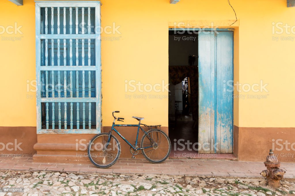 Old bike against yellow painted house in Trinidad, Cuba. stock photo