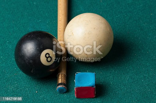 Old billiard ball 8 and stick  on a green table. billiard balls isolated on a green background.Black and white