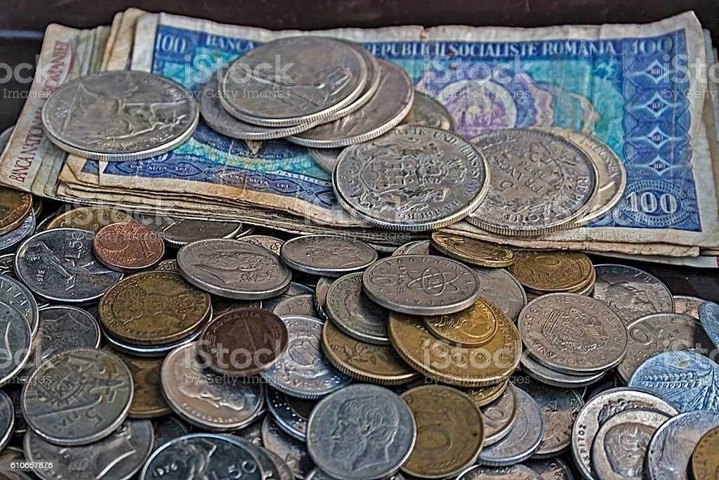 Old bills and coins of different nationalities stock photo