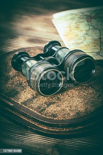 Old binoculars covered with patina on a wooden background.