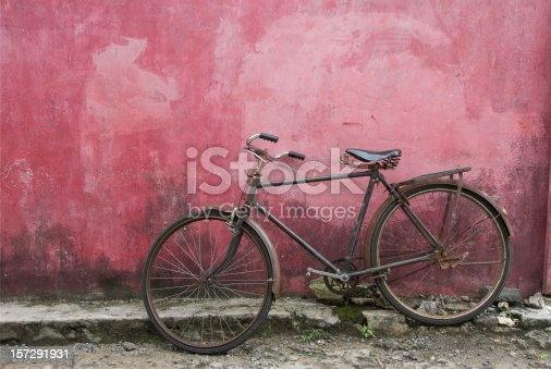istock Old black bicycle leaning against grunge pink wall 157291931
