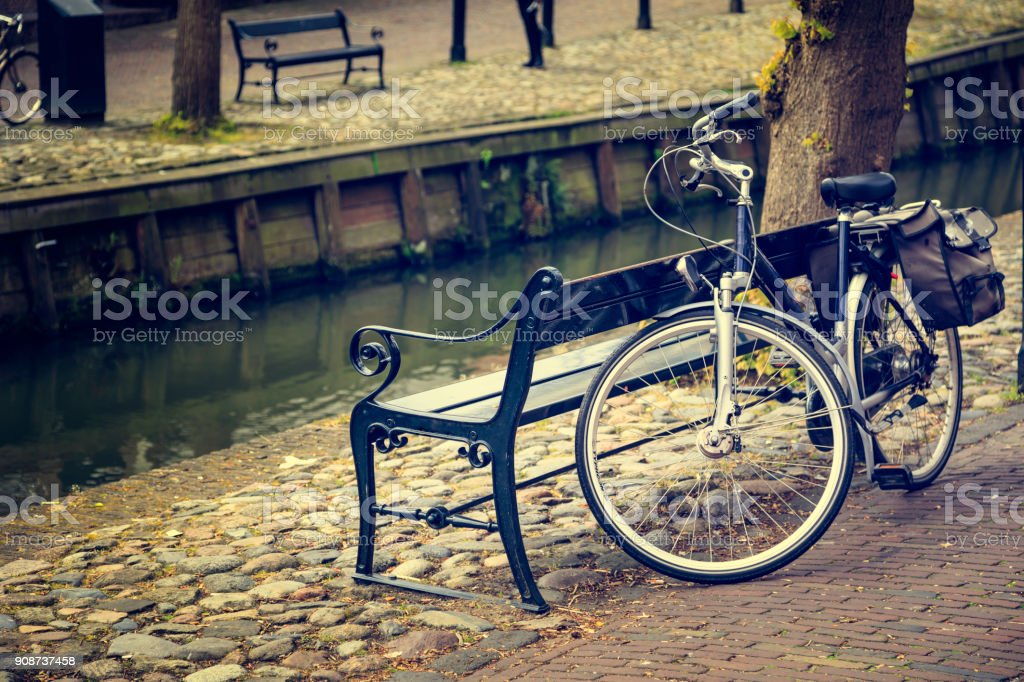 old black bicycle vintage bike parked in the street, near the canal Amsterdam Stock Photo