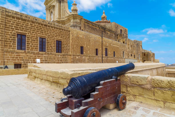 Old black canon on wooden stand at Saint John Bastion inside Cittadella - Castello acropolis in Victoria Town, part of UNESCO World Heritage Sites. stock photo
