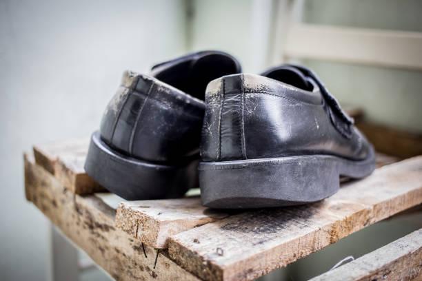 zapatos viejos de cuero negro sobre una plataforma - suministros escolares fotografías e imágenes de stock