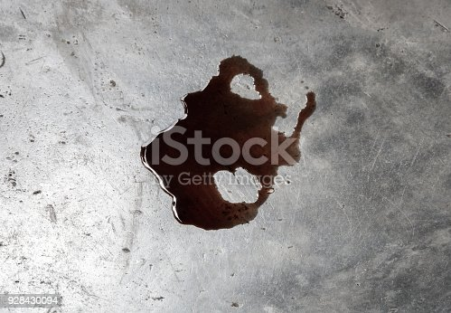 istock Old black oil motor car leak or drip on concrete floor on top view 928430094