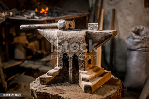 istock Old blacksmiths hammer on anvil in workshop read to be used for forging iron 1059352848