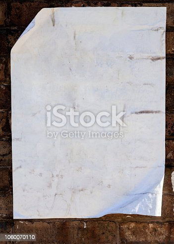 istock Old blank paper pasted on brick wall. 1060070110