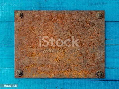 A blank rusty and weathered steel metal sign bolted by four bolts to a turquoise colored wooden paneled fence. Good copy space in the center of the metal plate.