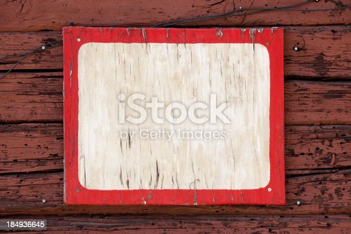 Red and white wooden weathered blank sign on red wood building.