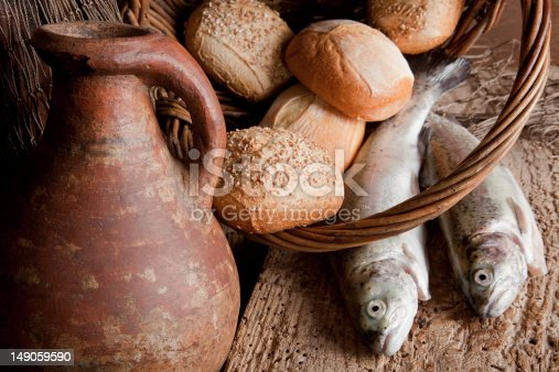 Religious still life of 5 loaves of bread, an antique wine jug and 2 fish
