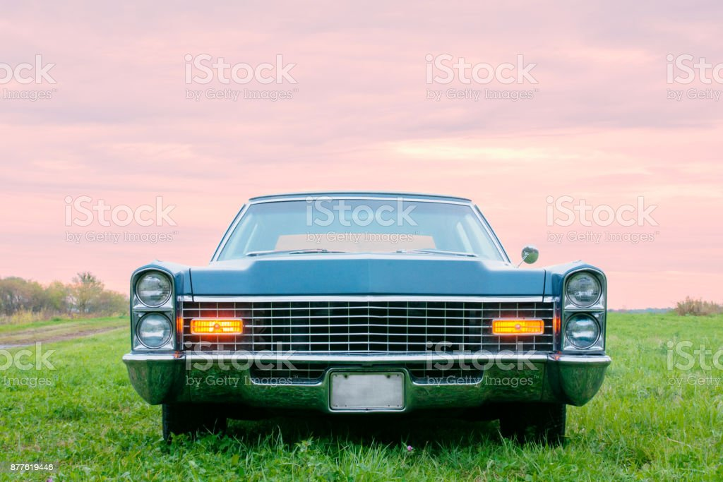 Old blue 1967 car parked at sunset in a field stock photo