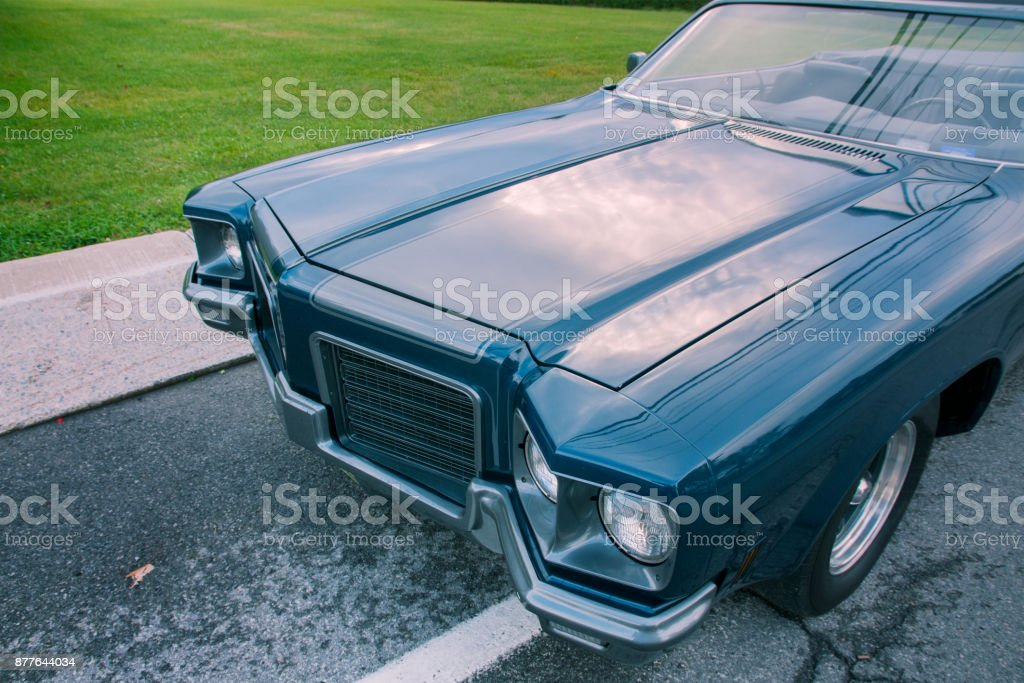 Old blue 1971 convertible car parked at sunset stock photo
