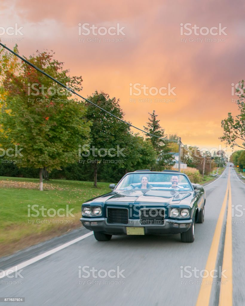 Old blue 1971 convertible car taking a ride at sunset stock photo