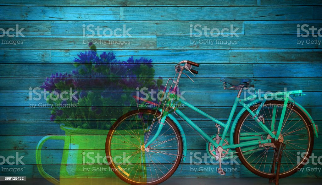 Old blue bicycle and flower in vas on wooden background , multiply effect stock photo