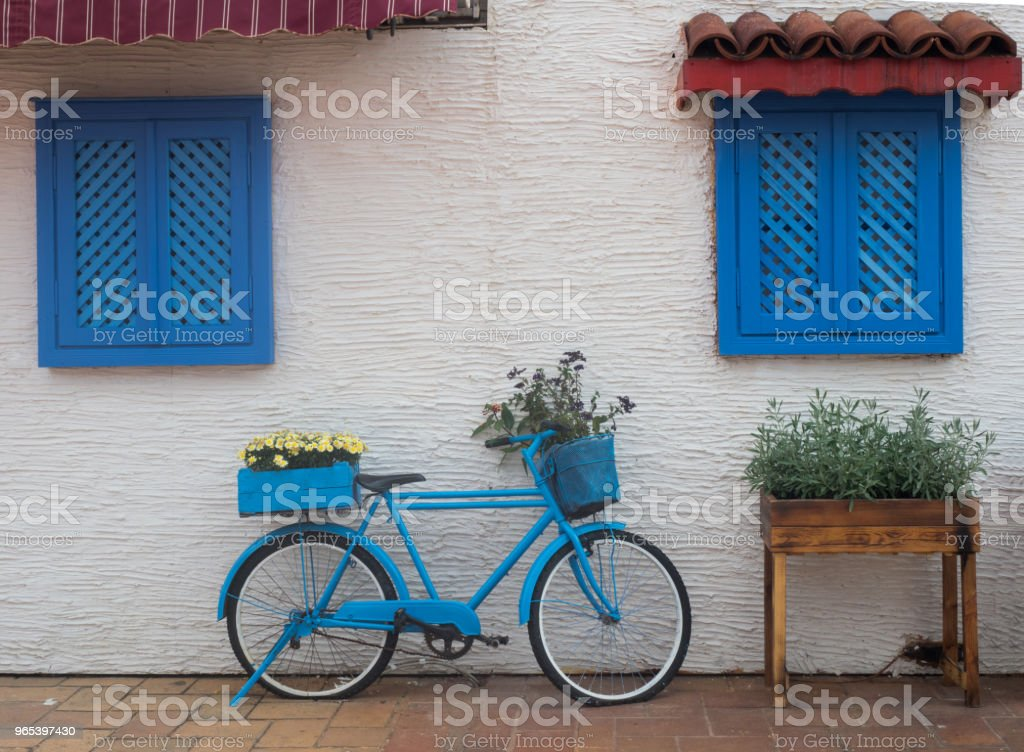 old blue bicycle stands on the street near the wall with windows with wooden shutters royalty-free stock photo
