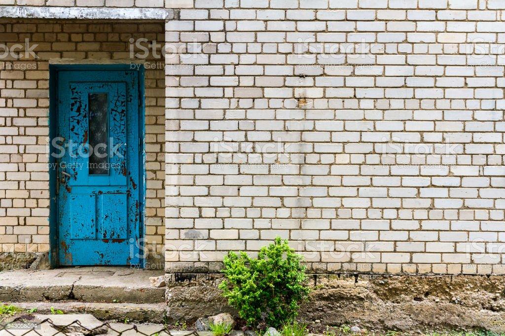 Antiga porta azul em uma parede de tijolos brancos - foto de acervo