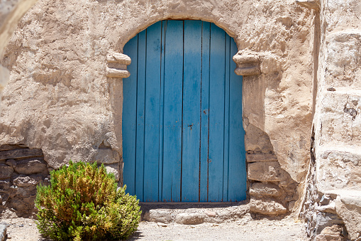 An old blue door of a deserted house in the village of Isluga, which is situated in the arid Andean altiplano near Iquique, Northern Chile.