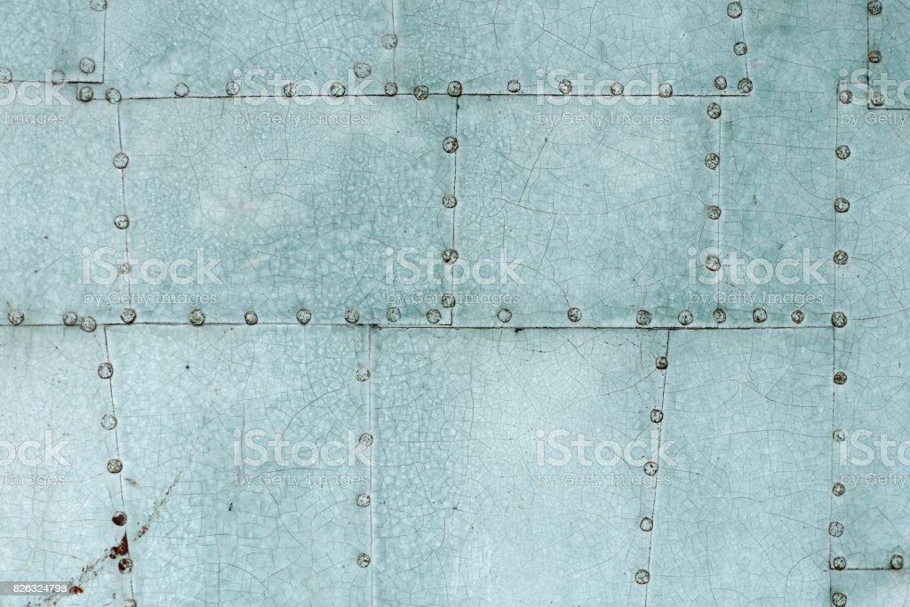 Old blue painted riveted metal door detail stock photo