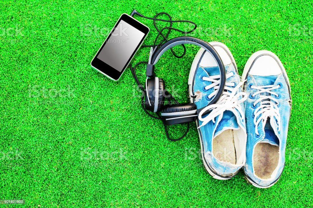 Old blue shoes with phone and headphones on the green grass. stock photo