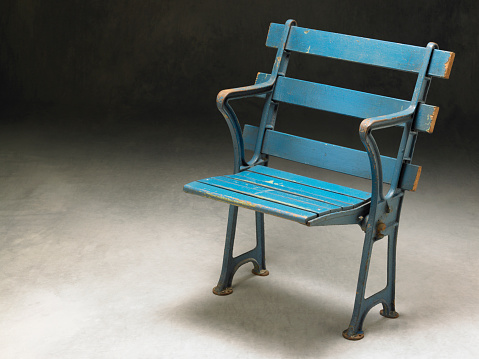 An antique baseball stadium seat. Horizontal shot with lots of copy area.
